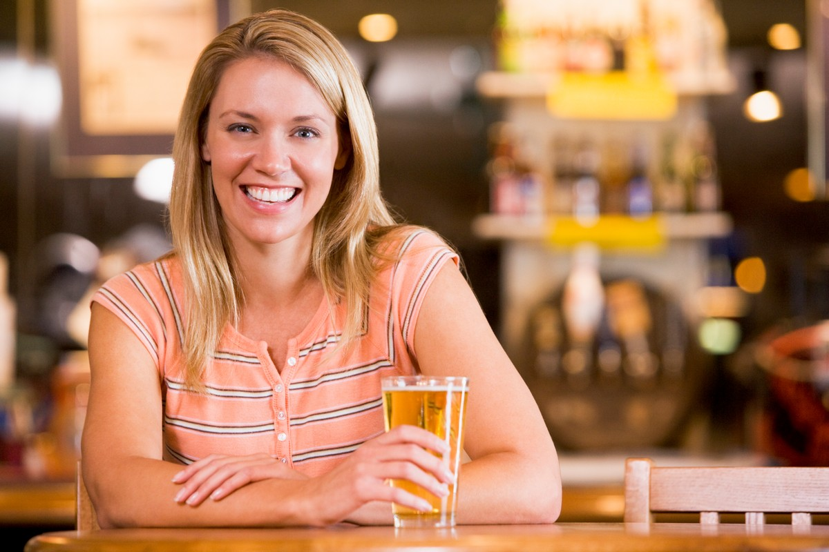 young-woman-enjoying-a-beer-at-a-bar